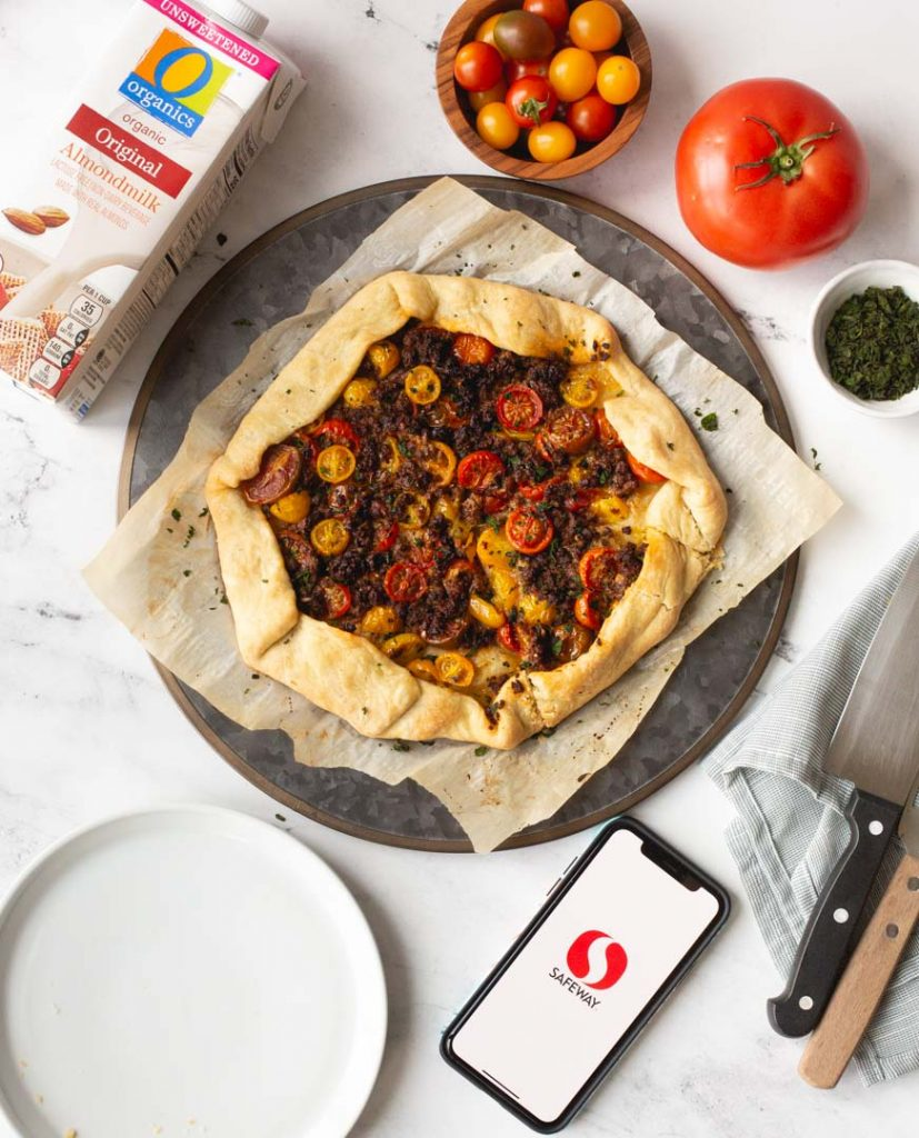 top down view of a tomato galette with impossible italian sausage, with o organics almond milk and fresh tomatoes