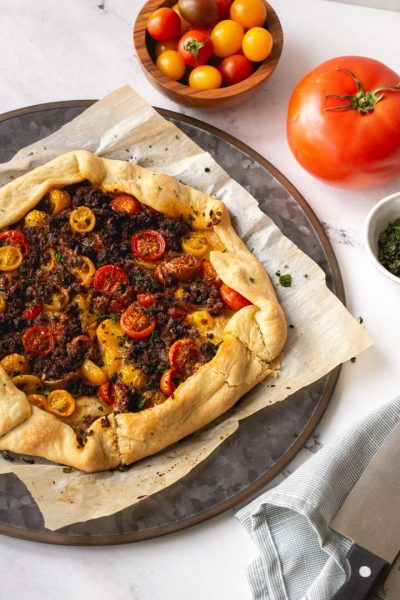 tomato galette with impossible meat and basil on a serving plate