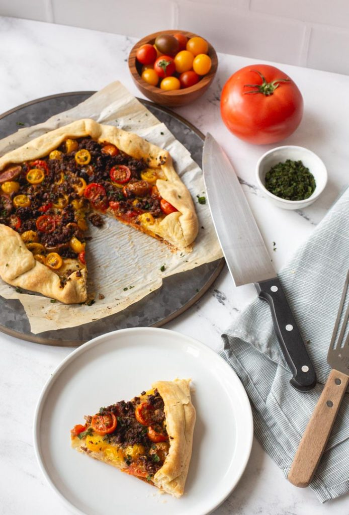 tomato galette with impossible meat and fresh basil on a serving dish with a slice removed