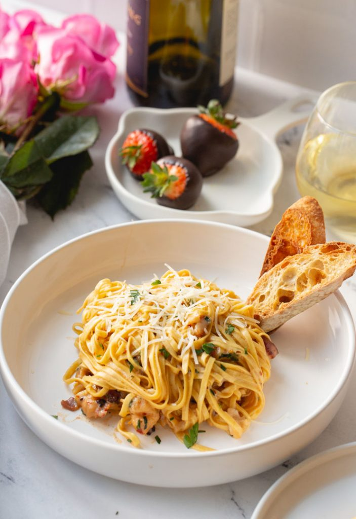 creamy lobster pasta in a dish with toasted sourdough bread, chocolate covered strawberries and pink roses