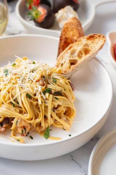 creamy lobster linguine in a bowl with two slices of sourdough bread